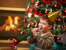 Little boy at new year's eve. Little boy laughing on new year's eve, wearing shiny hat and blowing horn, looking at camera, christmas tree in background Stock Images