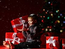 Little boy on the eve of new year and christmas is sitting under the tree. A little boy on New Year`s Eve and Christmas is sitting under the Christmas tree and stock images