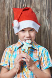 Little boy in New Year's red cap eats Christmas cookies Royalty Free Stock Photo