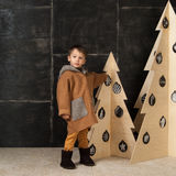 The little boy next to decorative Christmas trees Stock Images