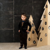 The little boy next to decorative Christmas trees Royalty Free Stock Image