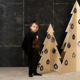 The little boy next to decorative Christmas trees Royalty Free Stock Images