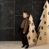 The little boy next to decorative Christmas trees Royalty Free Stock Photography