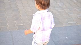 Little boy with nipple running. Down the street stock footage