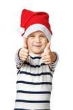 Little Boy no chapéu de Santa com os polegares acima da aprovação do sinal isolados Fotos de Stock