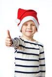 Little Boy no chapéu de Santa com os polegares acima da aprovação do sinal isolados Imagens de Stock Royalty Free