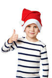 Little Boy no chapéu de Santa com os polegares acima da aprovação do sinal isolados Imagem de Stock Royalty Free