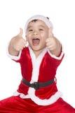 Little Boy no chapéu de Santa com os polegares acima da aprovação do sinal isolados Fotos de Stock Royalty Free