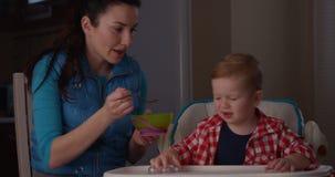 Little Boy no quiere comer el desayuno y a la madre gritadora que intentan alimentar al niño almacen de video