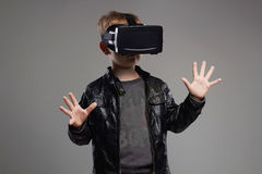 Little Boy nos vidros da realidade virtual que jogam o jogo Caçoa o divertimento Fotografia de Stock