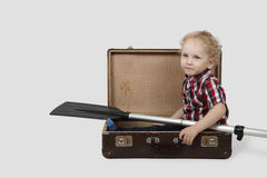 Little boy with oar sits in vintage suitcase Stock Photo