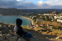 Little boy observing sea and city from the hill Stock Images
