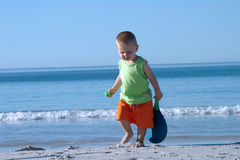 Little boy and ocean. A little cute chubby boy walks on the beach with a tennis ball and a racket in his hands and gentle waves wash the shore in back ground Royalty Free Stock Image
