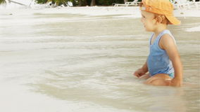 Little boy on the ocean beach. Little boy sitting in the sand on the ocean beach happy about waves stock footage