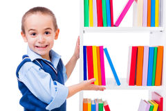 Little boy offering books on shelf Royalty Free Stock Images