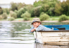 Little boy in old boat on the calm lake surface Royalty Free Stock Photography