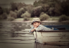 Little boy in old boat on the calm lake surface Stock Photos