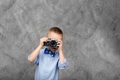 Little boy with an old camera against gray textured background Royalty Free Stock Image