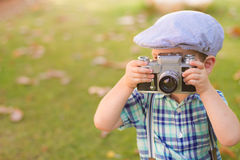 Little boy with an old camera shooting outdoor. using a vintage retro film cam. summer field. stock image
