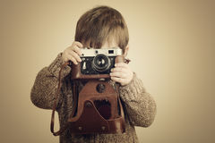 Little boy with an old camera. Little boy taking pictures with old retro camera stock photo