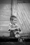 Little boy on old dock (BW). A black & white of a happy smiling little 4 year old boy sitting on an old abandoned loading dock barn with bare feet. Shallow depth Royalty Free Stock Photos