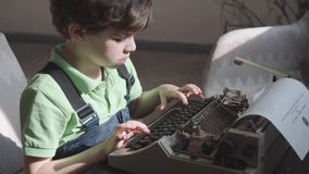 Pleased little six-year-old boy studies the work of an old typewriter. Little boy with the old typewriter, close up stock video