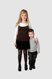 Little boy and older girl stand embraced stock photo
