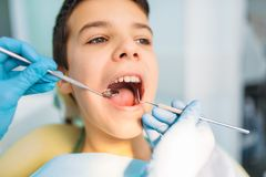 Little boy with open mouth in a dental cabinet. Pediatric dentistry. Female dentist looking for caries stock photography