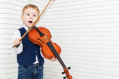 Little boy opened his mouth in surprise and holding a violin Royalty Free Stock Photography