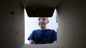 Little boy opening a carton with gift, bottom up view. Little boy opening a carton with gift stock video