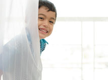 Little boy opening the door curtain Stock Photography