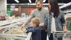 Little boy is opening freezer and taking pack of frozen vegetables then giving it to his daddy while shopping in. Supermarket with his family. People and food stock video footage