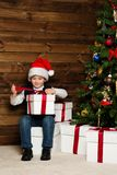 Little boy opening gift box under christmas tree Royalty Free Stock Photos