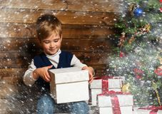Little boy opening gift box under christmas tree. In wooden house interior Royalty Free Stock Images