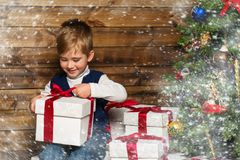 Little boy opening gift box under christmas tree Royalty Free Stock Images
