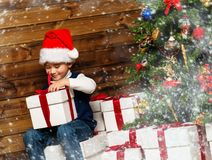 Little boy opening gift box under christmas tree. In wooden house interior Stock Photos
