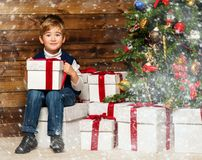 Little boy opening gift box under christmas tree. Little boy with gift box under christmas tree in wooden house interior Royalty Free Stock Photo