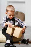 Little boy opening a gift in Christmas decorations waiting for a Stock Photos