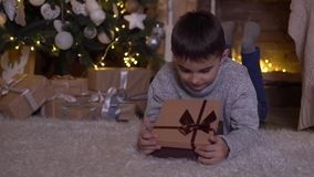 A little boy opens a box with a gift and rejoices lying on the floor near the Christmas tree. 4K. A little boy opens a box with a gift and rejoices lying on the stock video footage