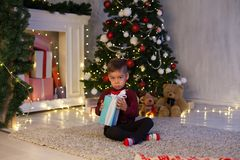 Little boy opens Christmas presents new year Christmas tree Garland royalty free stock photography