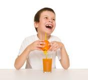 Little boy with orange juice Stock Photos