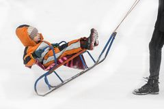 Little boy in orange jumpsuit being driven on a sled.  stock image
