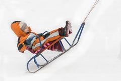 Little boy in orange jumpsuit being driven on a sled.  royalty free stock photo