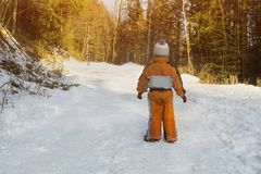 Little boy in an orange jumpsuit standing on snow-covered road in a coniferous forest. Mother is in a distance. Winter sunny day. royalty free stock image