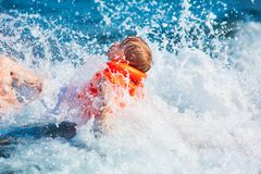 Little boy in orange life jacket swimming in the sea with waves with big splashes royalty free stock images