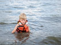 Cute little boy in orange life vest swimming in the river. Little boy in orange life vest swimming in the river royalty free stock image
