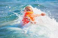 Little boy in orange life vest swimming in wave sea stock photo