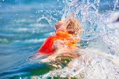 Little boy in orange life vest swimming in wave sea stock image
