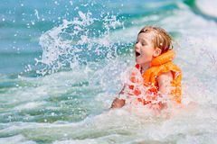 Little boy in orange life vest swimming in wave sea stock photography