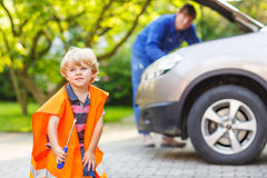Little boy in orange safety vest during his father repairing family car royalty free stock images